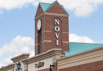 Tall brick tower with a green roof on top of a building. The tower has a clock on the front and lettering that reads Novi