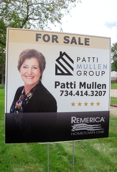 For sale sign used for selling a house that has a picture of Patti Mullen next to a house shaped logo that says Patti Mullen Group
