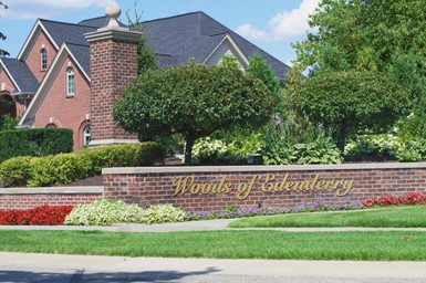The front entrance of a neighborhood in Northville with a sign in front of a large brick home that says The Woods of Edenderry