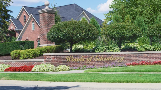 The front entrance for a Neighborhood in Northville, Michigan with letters engraved on a brick wall that reads the Woods of Edenderry