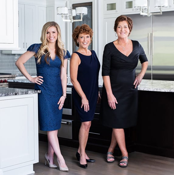 Group picture of three real estate agents at The Patti Mullen Group. Patti Mullen is in a black dress on the right with Carol Schrauben in a navy blue dress in the center and Megan Atkinson in a light blue dress on the left.
