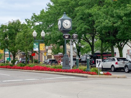 The center of downtown Plymouth, mi showing a clock next to some cross roads. The City has a 19th Century look to it
