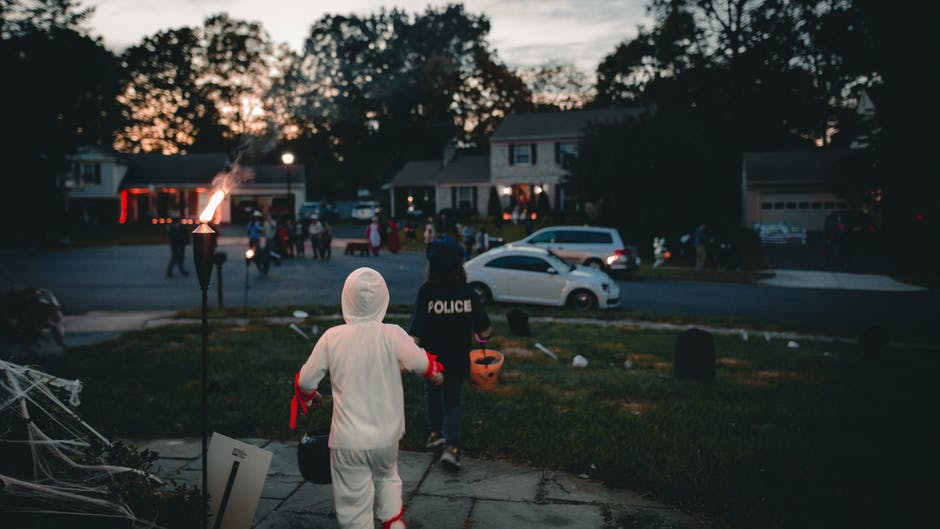 Kids on Halloween running toward homes in costumes in the Northville Neighborhood of Maple Hill